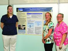 Three nurses display residency poster