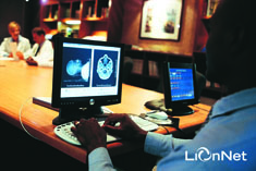 Physician using LionNet monitor to view scans