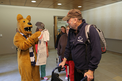 On his way out, Bob Phillips is greeted by the Nittany Lion, who presents him with a ballcap and a t-shirt signed by well-wishers.