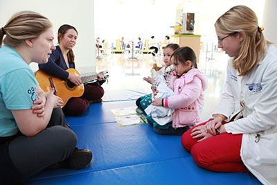 The teddy bears and the children enjoy a music therapy session.