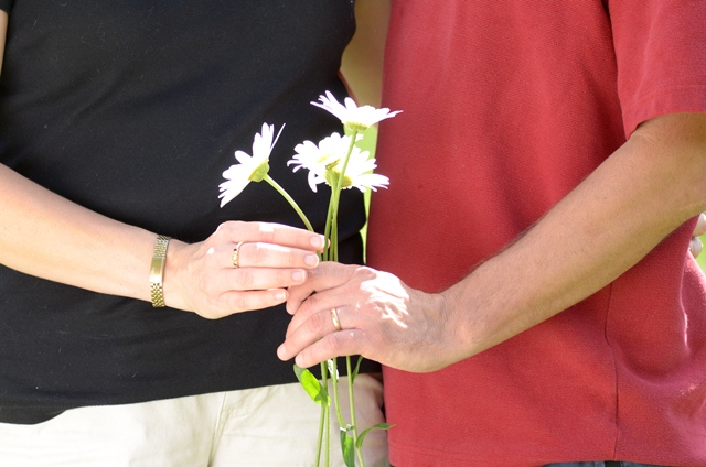 Melissa and Chris Masse holding flowers between them where their scars forever bind them as recipient and donor.