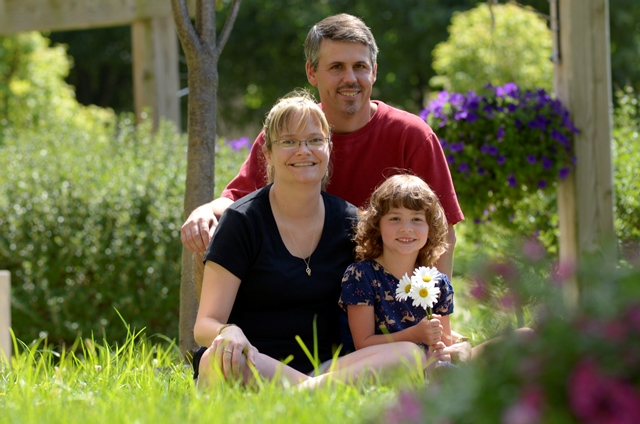 Chris, Melissa, and Katie Masse pose for a family portrait in the Garden of Life at Penn State Milton S. Hershey Medical Center.