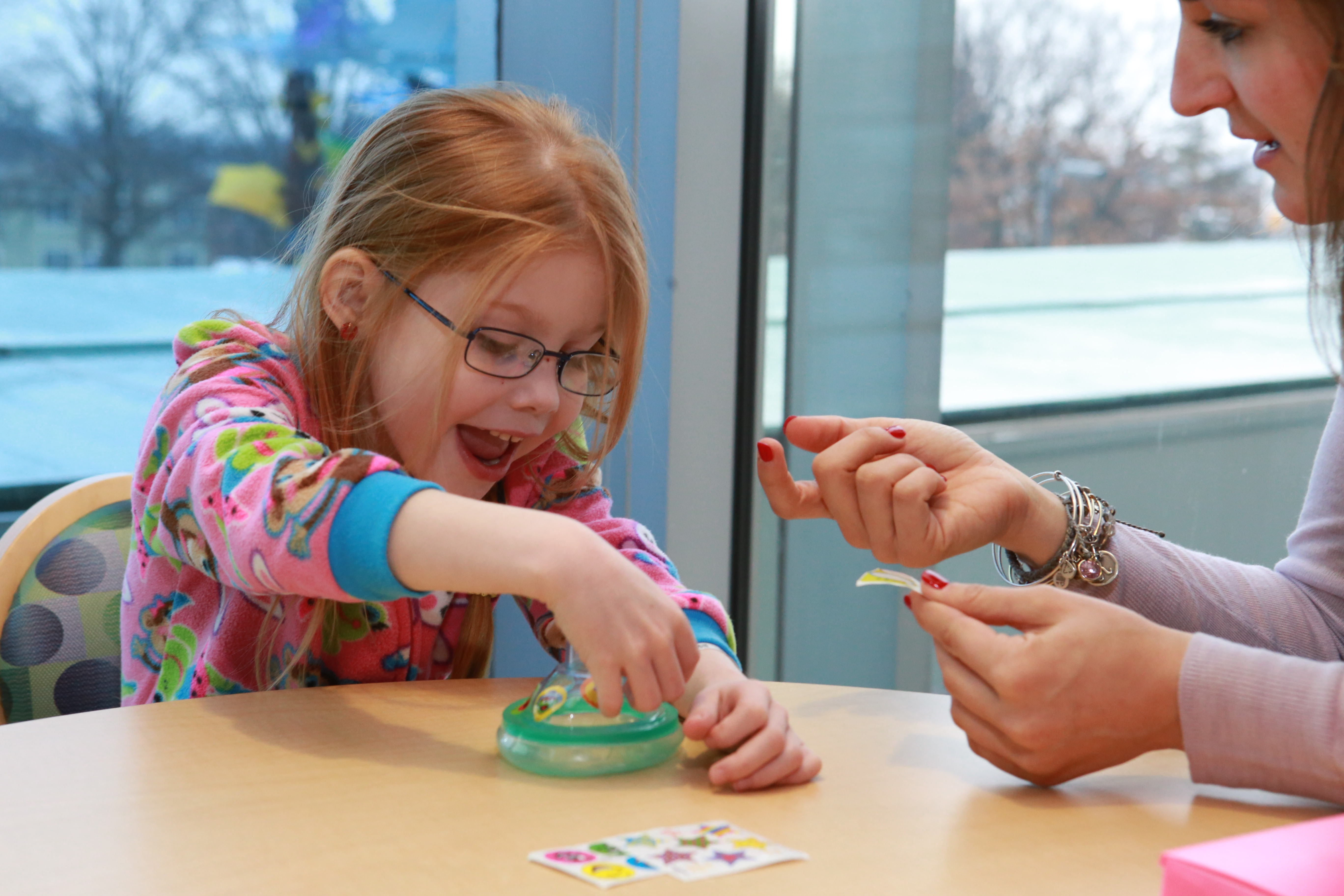 """Kate Denlinger, certified child life specialist helps patient Kaitlyn Teeter, 5, decorate her anesthesia mask with stickers prior to a procedure she regularly receives at Penn State Hershey Children's Hospital. """"Instead of coping with a bad diagnosis, she just has to cope with the routine of coming in so that she can continue being healthy,"""" Kate says."""