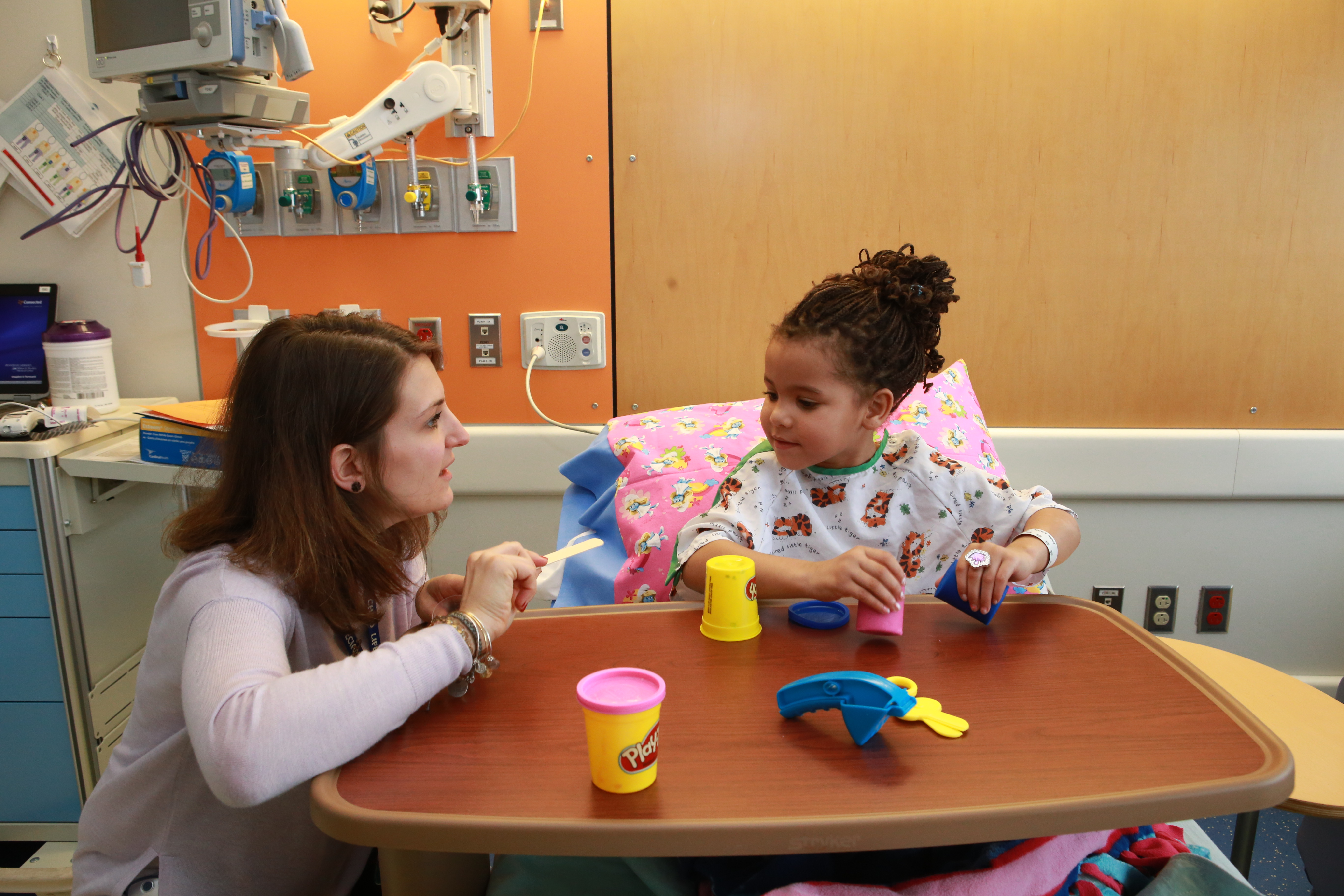 Kate Denlinger, certified child life specialist, shows Meney Richards, 5, how medicine cups and tongue depressors can be used to play with Playdoh.  Meney brought her Frozen-themed blanket for her surgery visit.