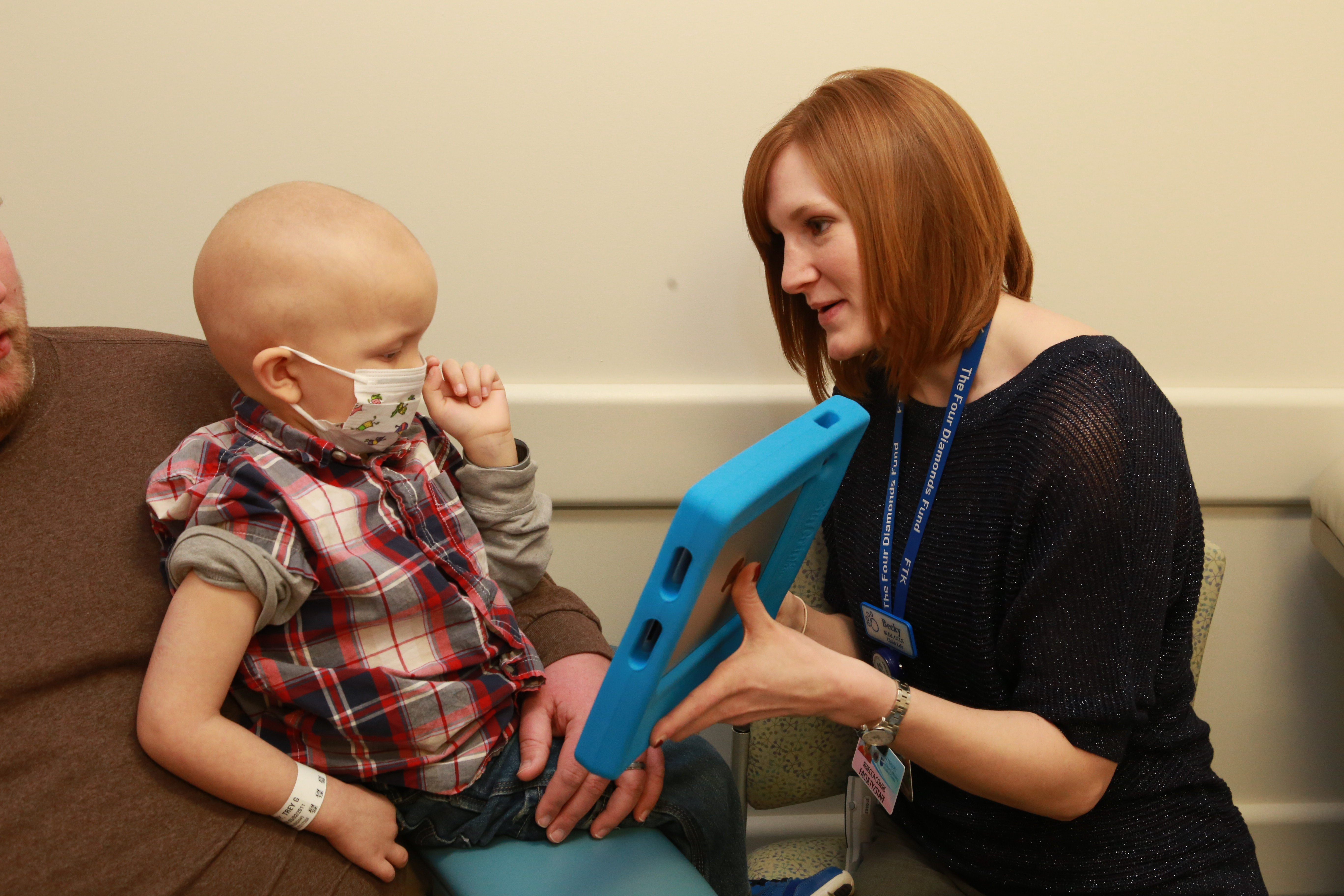 """Becky Combs, certified child life specialist, works to distract Trey Fry, 3, during a visit to Penn State Hershey Children's Hospital. Trey is questioning extra instruments he noticed on the nurse's tray. Becky explains they're not for him and that he's there only for the catheter changer he's been told about. """"No surprises, remember?"""" she says."""