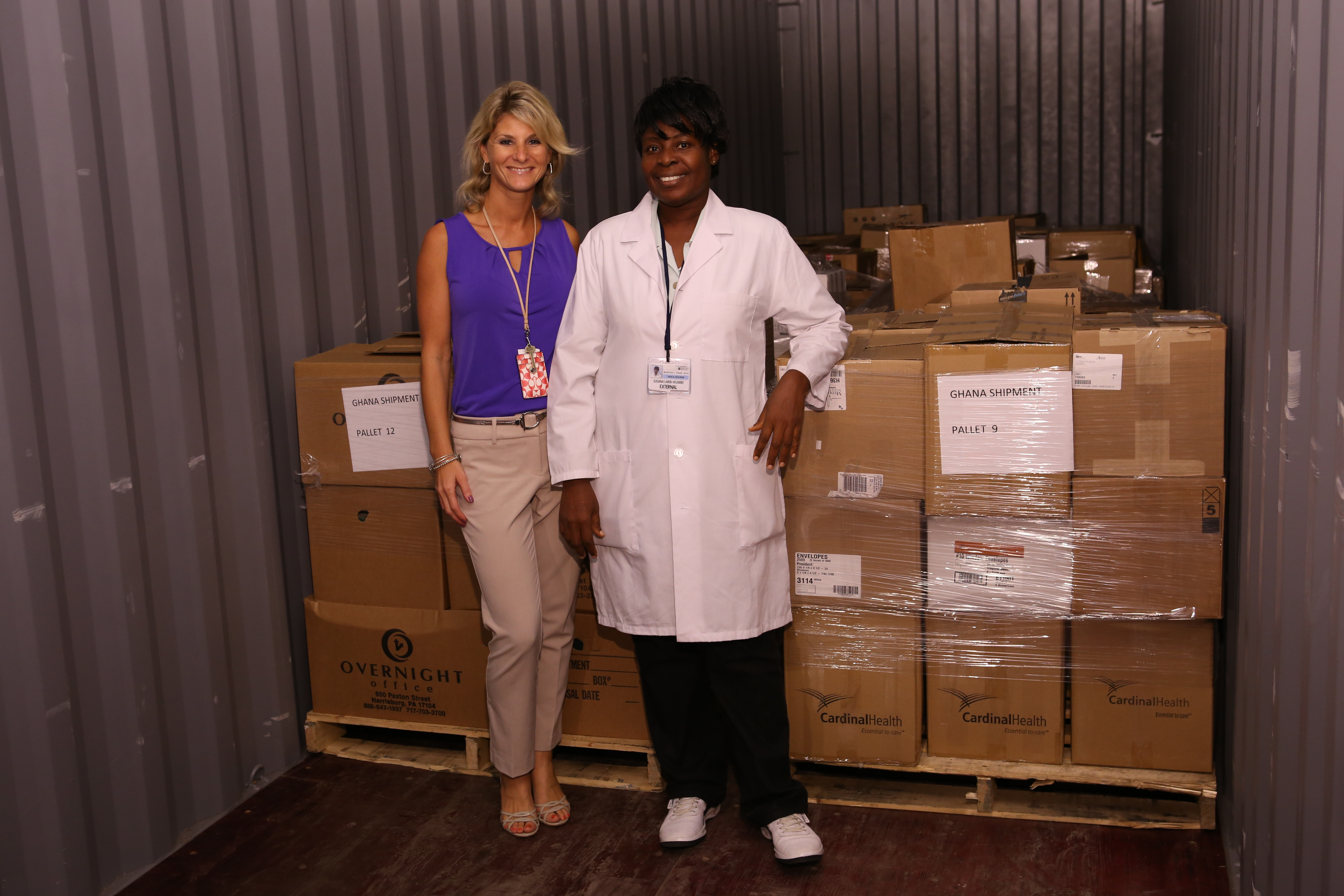 Penn State College of Medicine's Tina Engle with Susana Wumbee, a Mountcrest faculty member visiting the College of Medicine's Simulation Center for a six-month fellowship with a portion of the boxes full of donated medical education resources donated to Mountcrest College University.