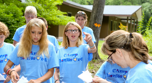 A teenage girl extends her fingers to see if an orange butterfly will alight upon them as a group of other teens stands around her, outdoors, all wearing blue Camp Lionheart T-shirts.