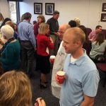 Attendees at an October 2015 party celebrate Roland Myers, who worked for 36 years on the Penn State College of Medicine electron microscopy team, on his retirement. The photos shows a room of people talking to each other in small groups, with a man in a light blue polo shirt most visible in the foreground and approximately 20 other people visible around him.