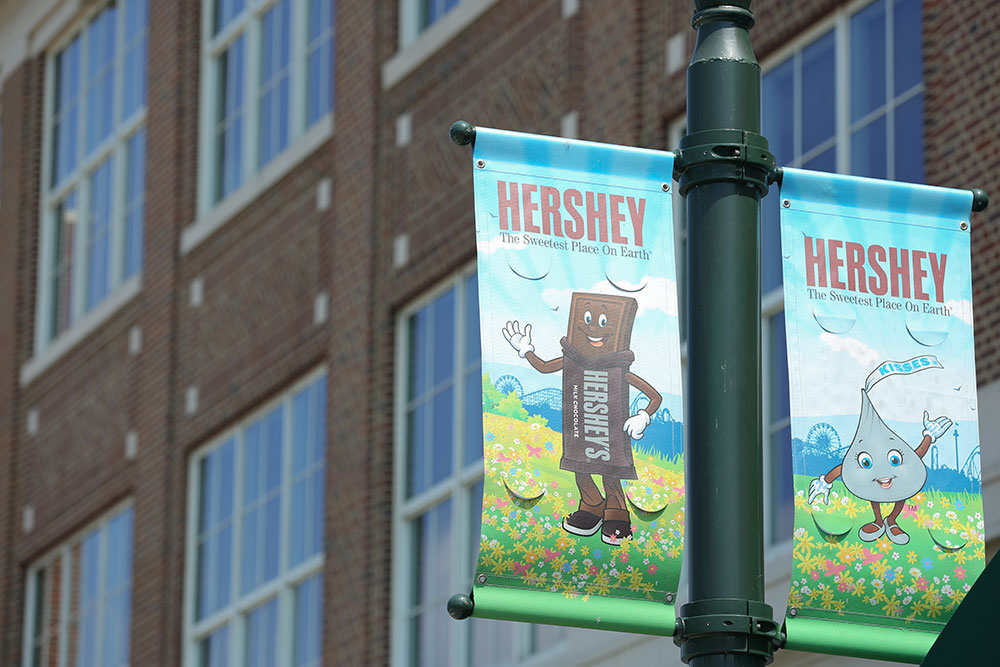 Two banners depicting cartoon candy characters are seen on a light pole in downtown Hershey, PA, in summer 2016, with a brick building with large glass windows in the background.