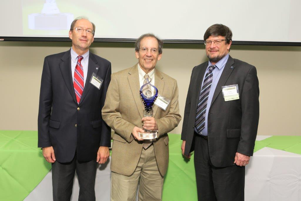 Ian Zagon, PhD, center, from the Department of Neural and Behavioral Sciences at Penn State College of Medicine, was the 2015 Innovator of the Year. The 2016 Innovation Awards ceremony will be Oct. 27, 2016. Three men are pictured; the men at left and right are wearing dark suits, and the man in the center is wearing a tan suit and holding a trophy, while smiling.