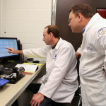 Todd Umstead, Research Project Manager, left, and E. Scott Halstead, MD, PhD, Director, right, are seen at work in the Pulmonary Immunology & Physiology Core in 2015. Umstead is at the center of the photo, looking left toward a computer screen and framed by lab equipment on the table in front of him. Umstead looks over his shoulder from the right of the photo.