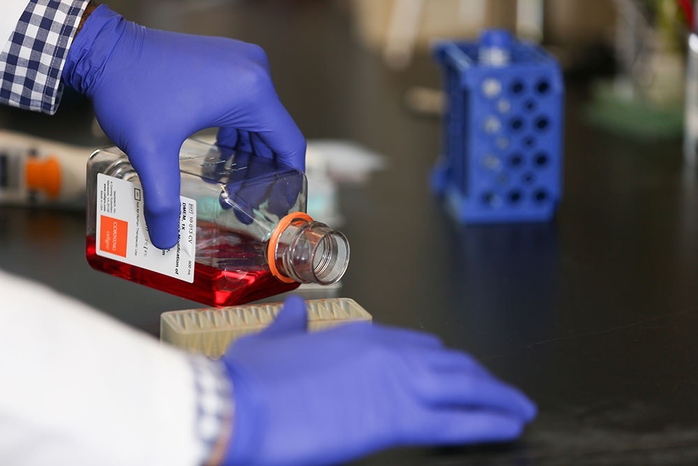 A close-up of a researcher's two gloved hands. The left hand is pouring a red liquid into a small container on a lab bench.