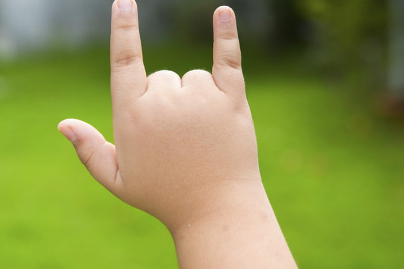 A child's hand gives a sign language motion.