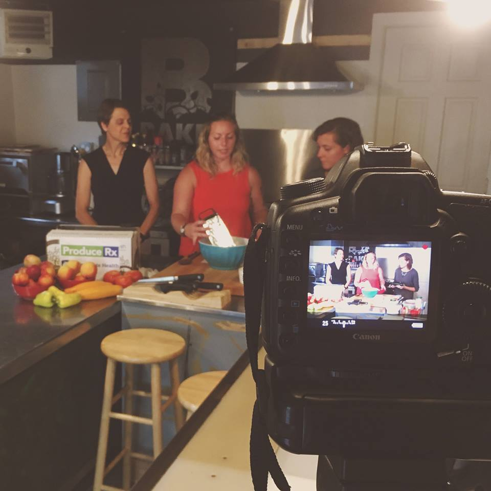 A photo of Produce RX staff being filmed preparing a recipe