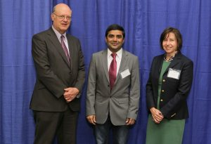 At the 2016 Penn State College of Medicine Innovation Awards, Dr. Raghavendra Gowda was named the 2016 Investigator to Watch. Gowda is pictured with A. Craig Hillemeier, MD, dean of Penn State College of Medicine and CEO of Penn State Health, and Leslie Parent, MD, vice dean for research and graduate studies for the College. The three are pictured with Gowda in the center, standing in front of a blue photo backdrop.