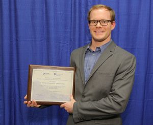 At the 2016 Penn State College of Medicine Innovation Awards, pharmacology department PhD student Sam Linton was recognized for his service to support commercialization and the research enterprise at the College of Medicine and Hershey Medical Center. Linton is pictured in front of a photo backdrop, smiling and holding a plaque with his award.