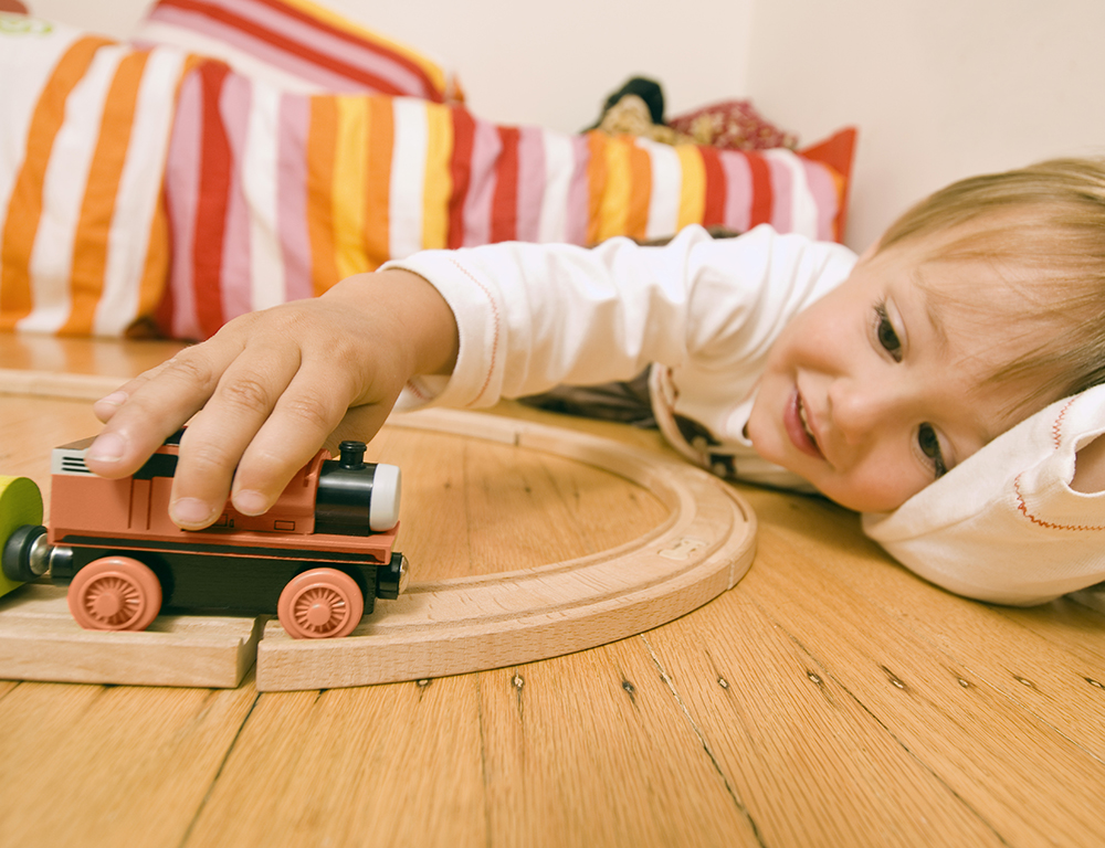 A child lays on the floor while playing with a toy train set.
