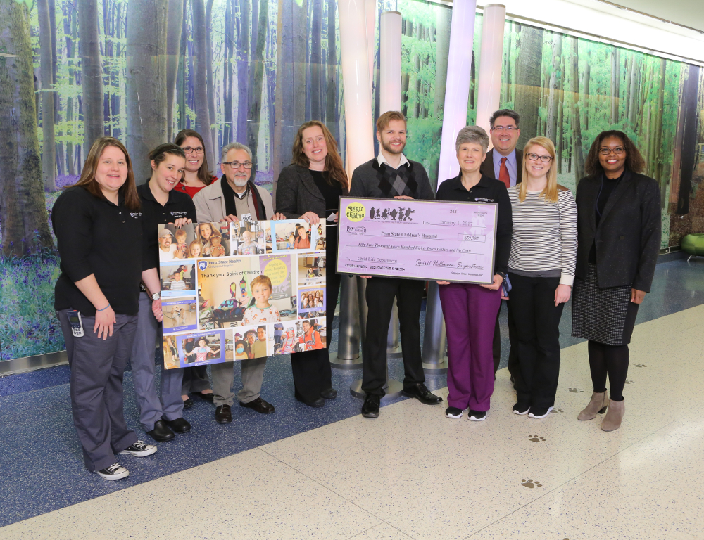 representatives of penn state childrens hospital and spirit halloween stores pose in the hospital lobby with