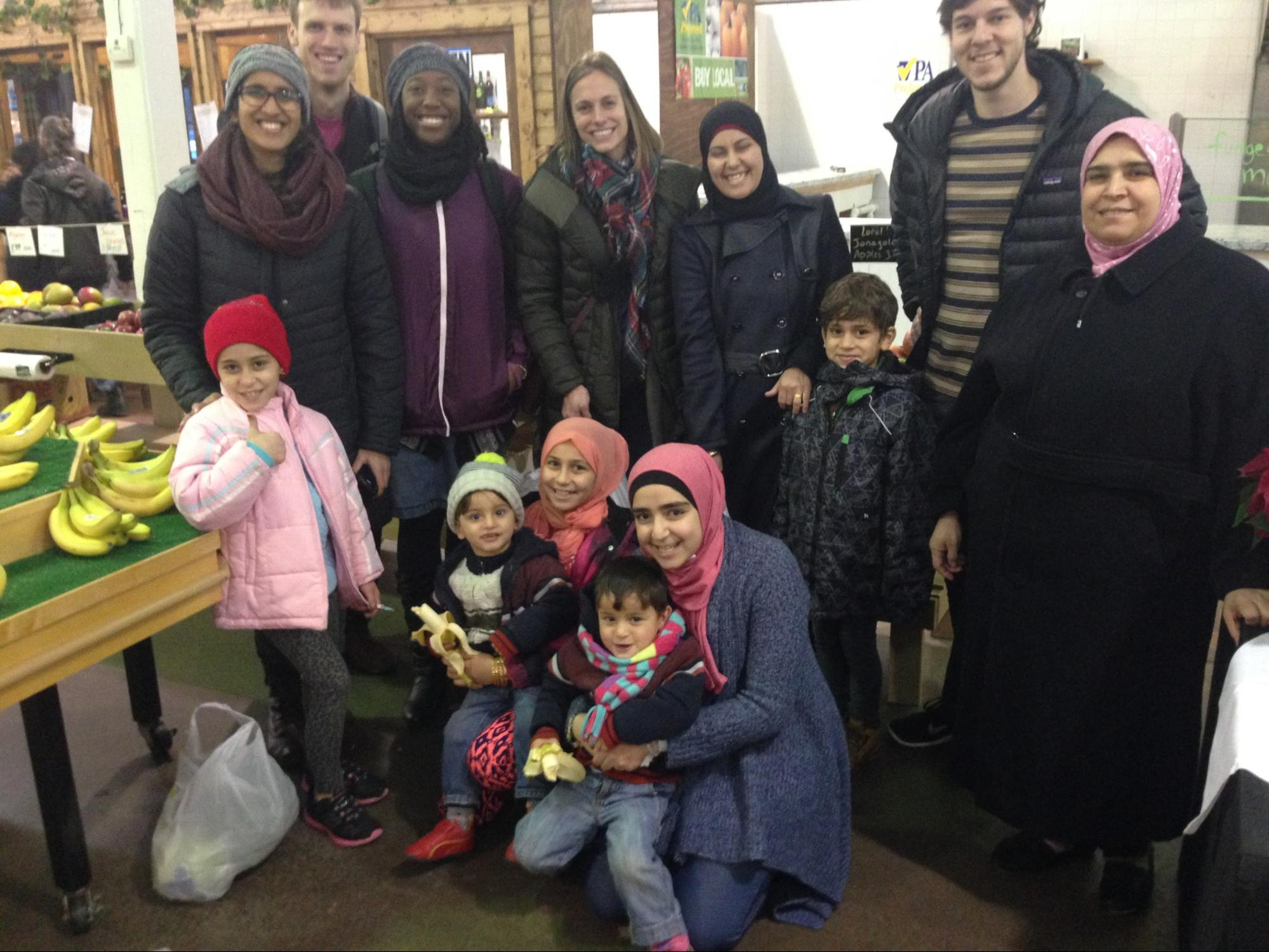 A photo of medical students with a refugee family at a farmer's market
