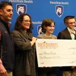 Four people pose holding an oversized check. They stand in front of a blue backdrop with the Penn State Health logo.