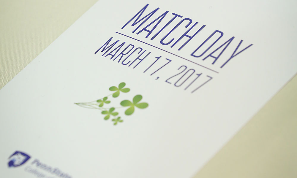 Match Day, in which fourth-year medical students learn their residency destinations, was held March 17, 2017. A program from the event is seen on a white tablecloth, with Match Day March 17, 2017 and the Penn State College of Medicine logo visible on the cover. Four shamrocks also appear, in honor of Match Day coinciding with St. Patrick's Day.