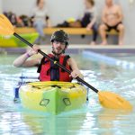 A man in an orange vest and black helmet is seated in a yellow kayak in a large swimming pool, paddling directly toward the camera.