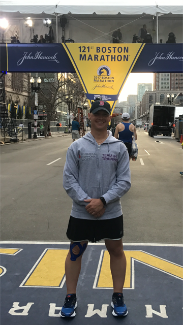 A photo of Tim Harner standing at the finish line of the Boston Marathon, sporting a ball cap and Team in Training hoodie