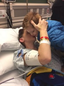 A young boy leans over a woman in a hospital bed as she holds his head with her right arm and kisses him on the cheek.