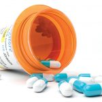 A brown-orange pill bottle lays on its side, surrounded by several blue and white capsules.