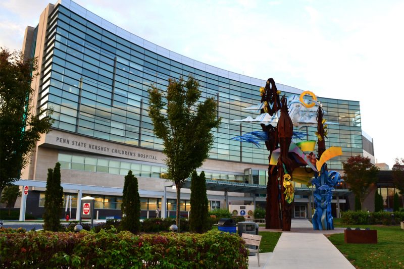 External view of Penn State Children's Hospital, during the day. A multi-colored metal sculpture and some trees and bushes are in the foreground.