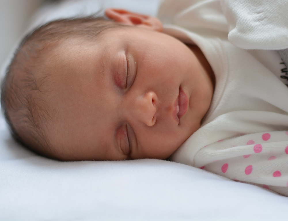 Close-up of a baby laying down sleeping, on a white sheet. The baby's white outfit has pink polka dots on the arms.
