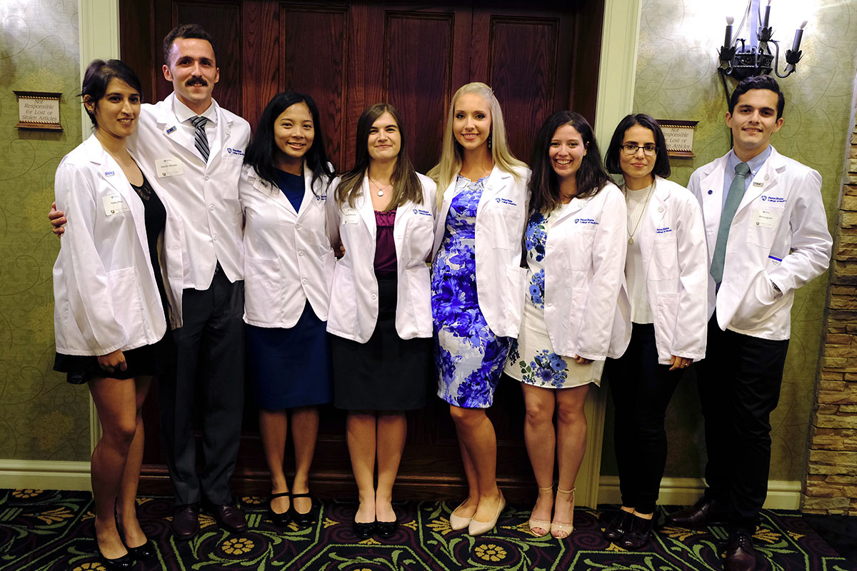 The MD/PhD program at Penn State College of Medicine welcomed eight new students during the 2017 MD Program White Coat Ceremony, held July 28. Pictured from left are new MD/PhD Medical Scientist Training Program students Trisha Basu, Vladimir Khristov, Maryknoll Palisoc, Hannah Bennett, Kristen Manto, Natella Maglakelidze, Nadia DiNunno and Morris Aguilar. The eight students are pictured standing in a large hall, in a single-file line against a wall. All are wearing short white coats denoting their status as medical students.