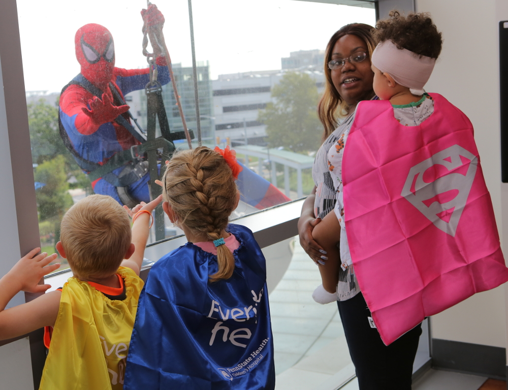 Three young children wearing capes, including a girl being held by her mom, look out a window at Spiderman, who is rappelling down the outside of the building.