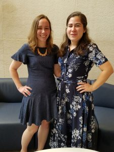 Sarah Tilden, left, and Elise Orellana, right, recently passed their comprehensive exams in the Penn State College of Medicine Anatomy PhD program. The two are pictured standing in a room with a tan wall and a blue seating area.