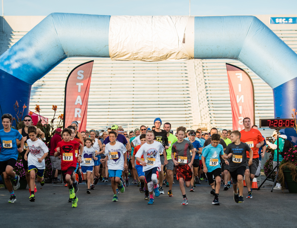 A group of children and adults in running clothes run through a large blue inflatable arch, underneath which there are signs reading 'start' and 'finish.'
