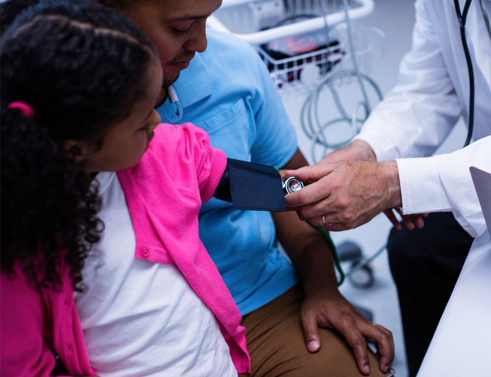 A young girl sits on her dad's lap while a physician (at right) takes her blood pressure from her left arm.