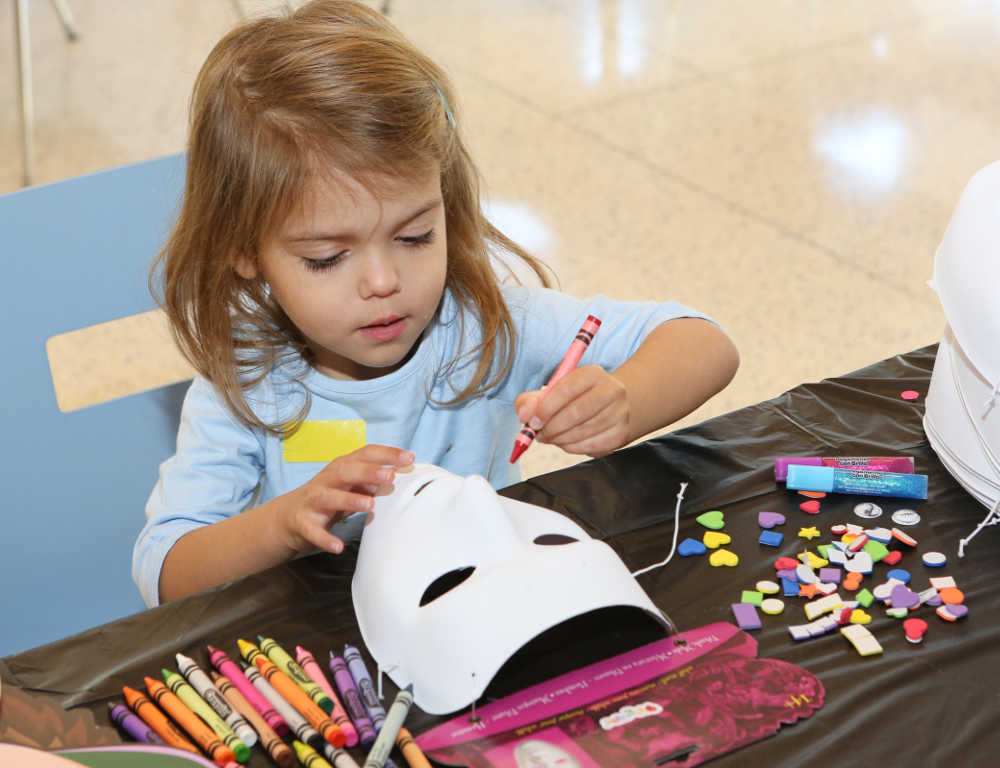 A young girl sits at a table, drawing on a white plastic mask with a red crayon. Other crayons and craft supplies are on the table near her.
