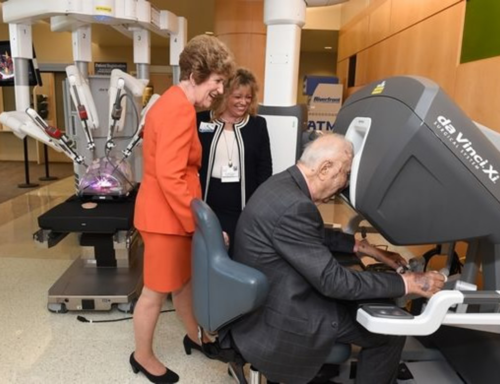 A man sites at the controls of a da Vinci Xi surgical system. Two women stand behind him, looking on.
