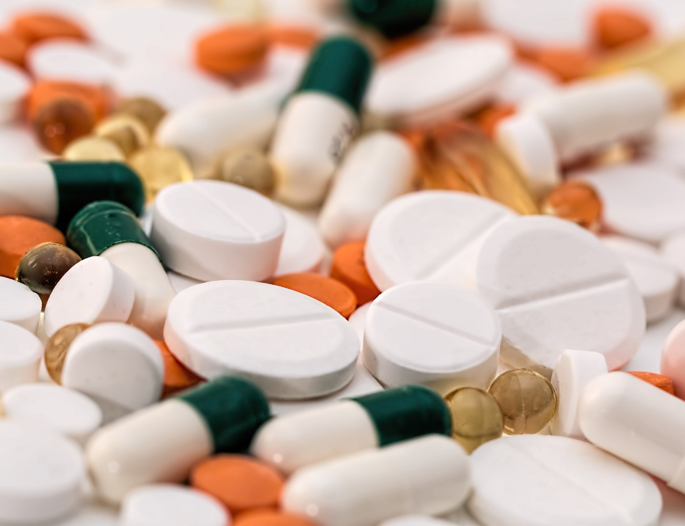 A close-up of a pile of medication, including white pills, orange pills and green and white capsules.