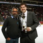 Two men pose for a photo, looking at the camera. The man on the right holds a small trophy. They are standing on an ice rink, where some young hockey players and fans are seen in the background.