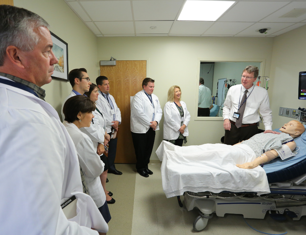 A man stands beside a hospital bed with a mannequin in it, speaking to a group of six people who are standing around the room's perimeter.