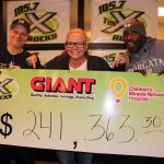 """Three people pose behind an oversized check in the amount of $241,363.30. It has logos for 105.7 """"The X,"""" Giant and CMN."""