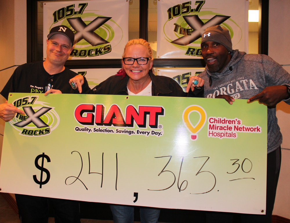 Three people pose behind an oversized check in the amount of $241,363.30. It has logos for 105.7