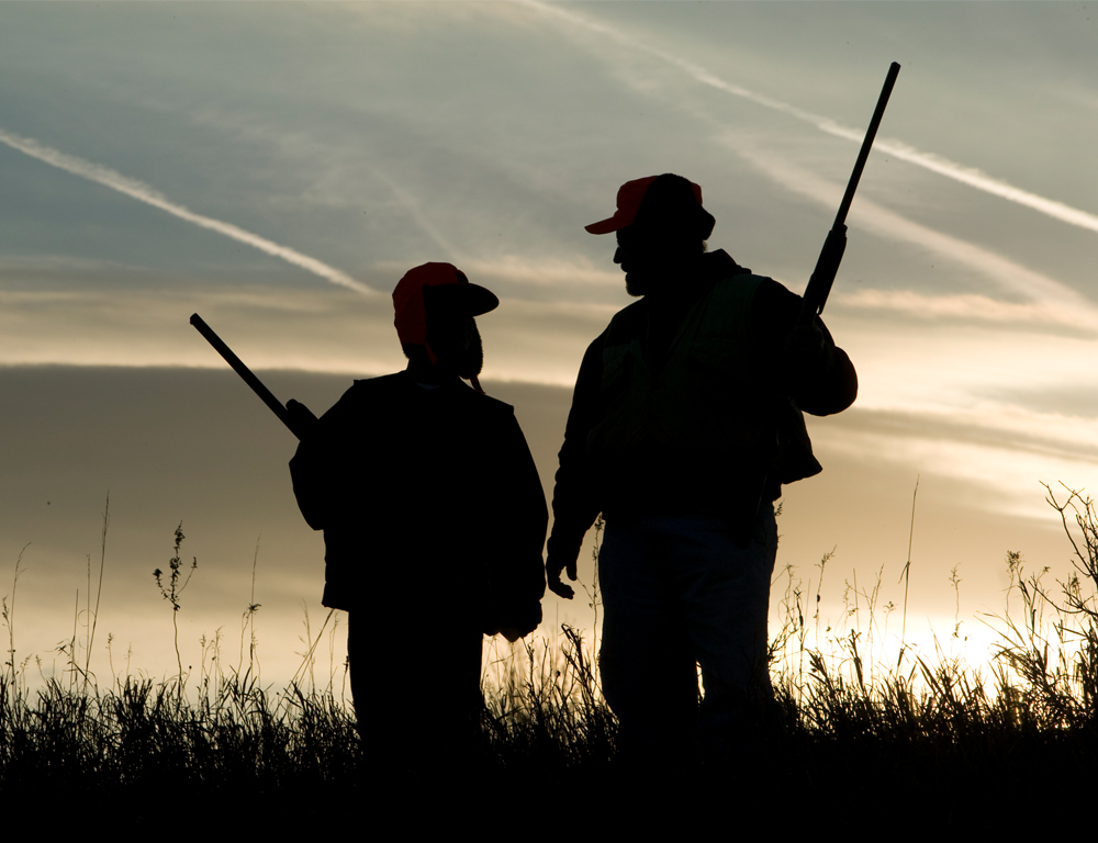 A silhouette of a man and a boy, each holding guns, standing in a field side-by-side. The sky is blue and gray, with some jet airplane vapor trails visible.