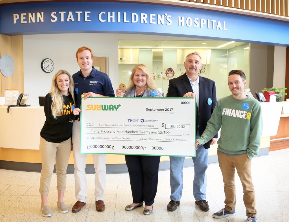 "Five people pose for a photo while holding an oversized check in the amount of $30,420.52, from Subway to ""Four Diamonds at Penn State Children's Hospital."""