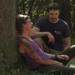 A woman in a purple tank top and obvious (mock) injuries to her right arm sits and leans against a tree. A man in a blue t-shirt kneels beside her.
