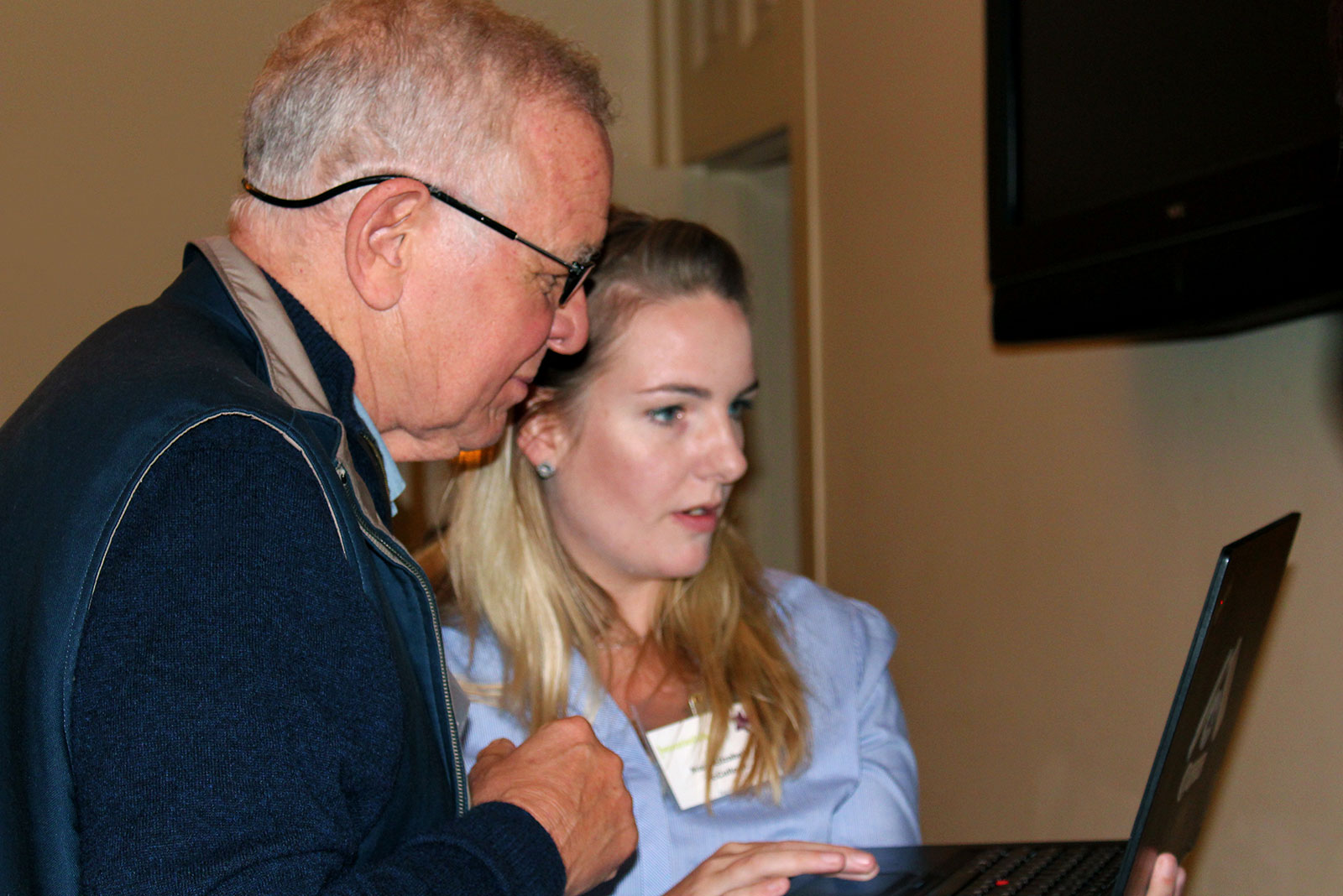 Mary Elizabeth McCulloch of VozBox demonstrates to Ed Arnold her team's accessible technology app for individuals with communication disabilities during the Oct. 17, 2017, Innovation Café at the Cocoa Beanery. The two are pictured standing side-by-side and looking at a laptop computer.