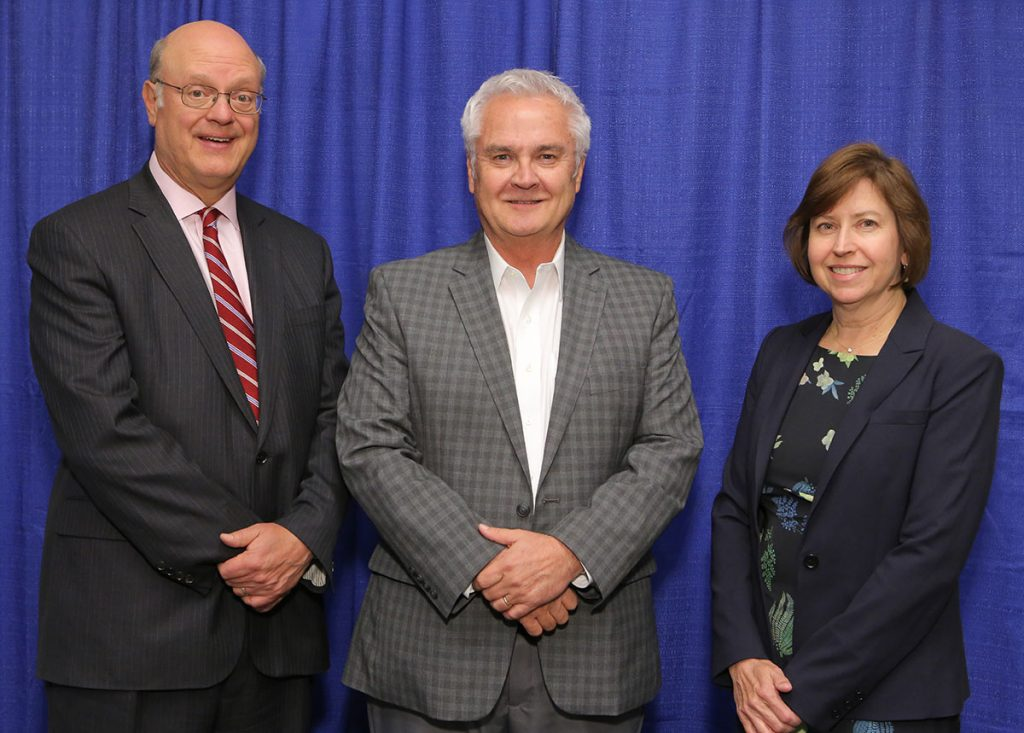 Penn State College of Medicine's 2017 Innovator of the Year award recipient is James Connor, PhD, center. Connor is pictured with, from left, A. Craig Hillemeier, MD, dean of the College and CEO of Penn State Health and Leslie Parent, MD, vice dean for research and graduate studies for the College. The three are pictured wearing professional dress clothing and standing in front of a blue photo background.