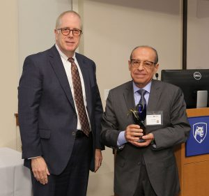 Penn State College of Medicine's 2017 Investigator to Watch award recipient is Elias Rizk, MD. Rizk was unable to attend the ceremony so accepting the award on his behalf was his father, Paul Rizk, right, shown with Kevin Harter, Director of the Center for Medical Innovation at Penn State College of Medicine. The two men are pictured standing in a large conference room with a podium in the back right of the photo.