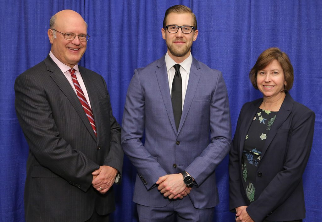 Penn State College of Medicine's 2017 Student Award for Excellence in Innovation award recipient is Oliver Mrowczynski, middle. Mrowczynski is pictured with, from left, A. Craig Hillemeier, MD, dean of the College and CEO of Penn State Health and Leslie Parent, MD, vice dean for research and graduate studies for the College. The three are pictured wearing professional dress clothes in front of a blue photo background.